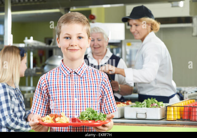 Male Pupil With Healthy Lunch In School Cafeteria - Stock Image