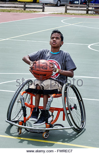 Florida FL Miami Tropical Park Paralympic Experience sports disabled basketball court wheelchair Asian boy shooting - Stock Image