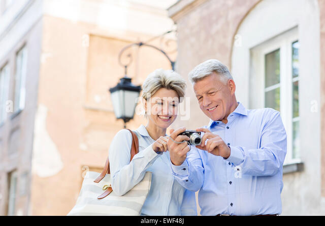 Happy middle-aged couple looking at pictures on digital camera in city - Stock Image