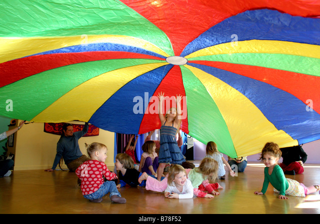 Released children playing under uplifted colorful parachute in play group California - Stock-Bilder