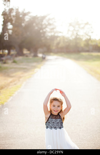 Portrait of girl on lane with arms above head - Stock-Bilder