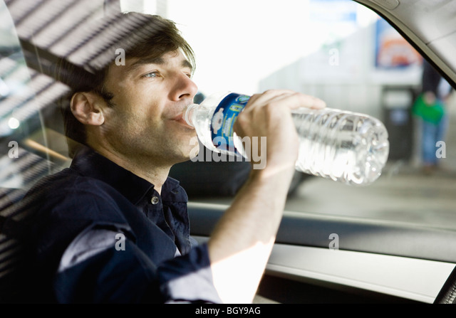 Man drinking bottled water while driving - Stock Image