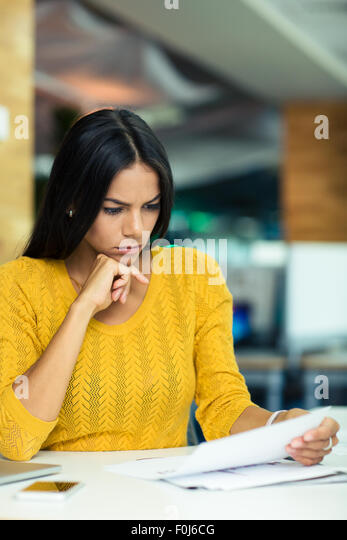 Portrait of a beautiful businesswoman reading documents in office - Stock Image