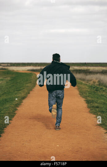 Middle aged man running in rural coastal area - Stock Image