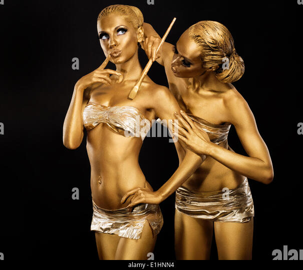 Body Art. Woman painting Body with Paint Brush in Golden Color. Gold Make Up - Stock Image