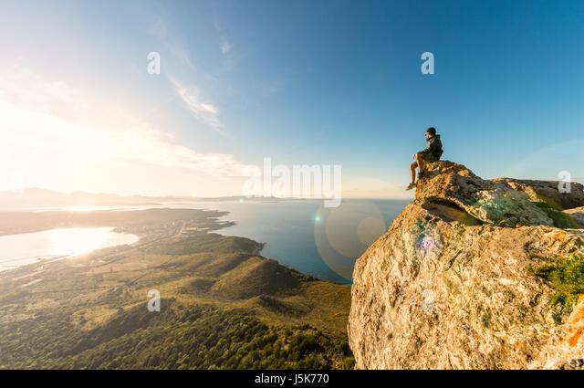 A traveler on the top of the mountain is enjoying the stunning view at sunset in Sardinia, Italy. - Stock Image