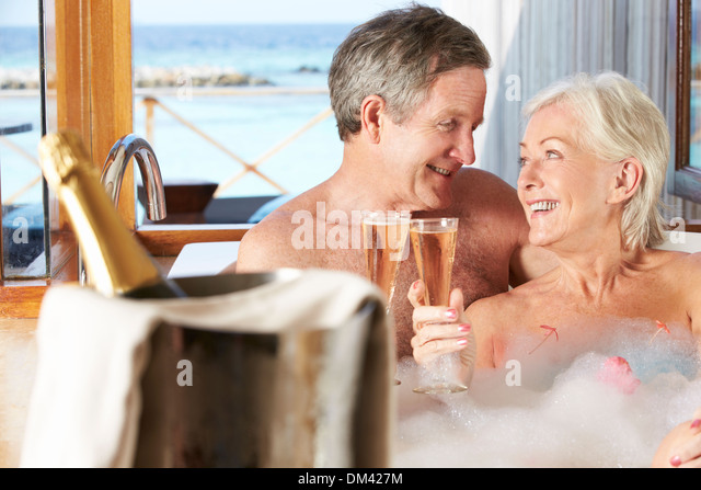 Senior Couple Relaxing In Bath Drinking Champagne Together - Stock-Bilder
