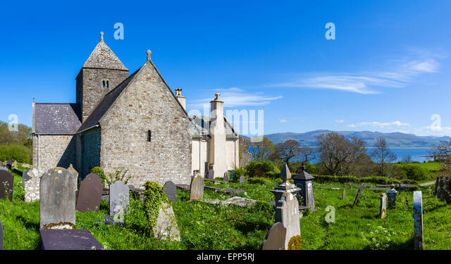 The 12thC St Seiriol's Church, part of historic Penmon Priory, with Snowdonia in the distance, Anglesey, Wales, - Stock Image