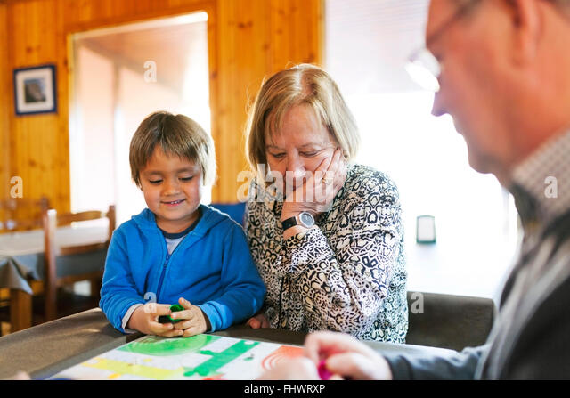 Grandparents playing ludo their grandson - Stock-Bilder