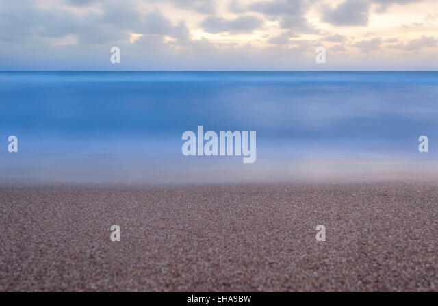 Minimalist view from the Florida beach of a flat calm ocean at sunrise with fluffy clouds in the sky. - Stock Image
