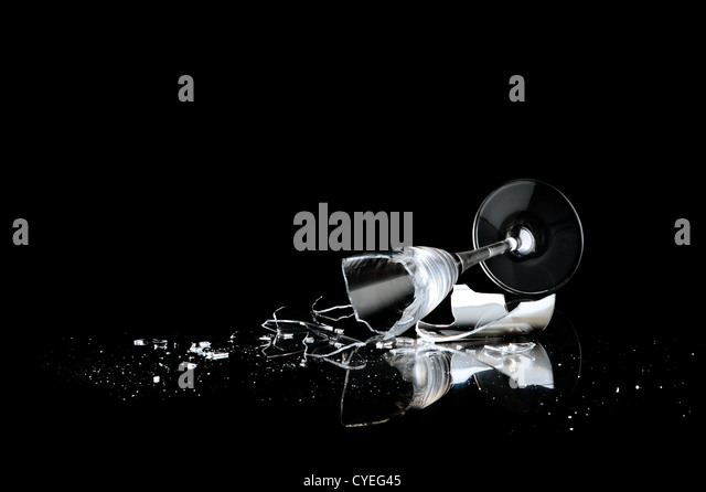 elegant wine glass broken on a dark background - Stock Image