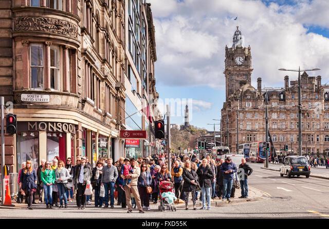 Crowd of people waiting to cross the road in Princes Street, Edinburgh, Scotland, UK - Stock Image