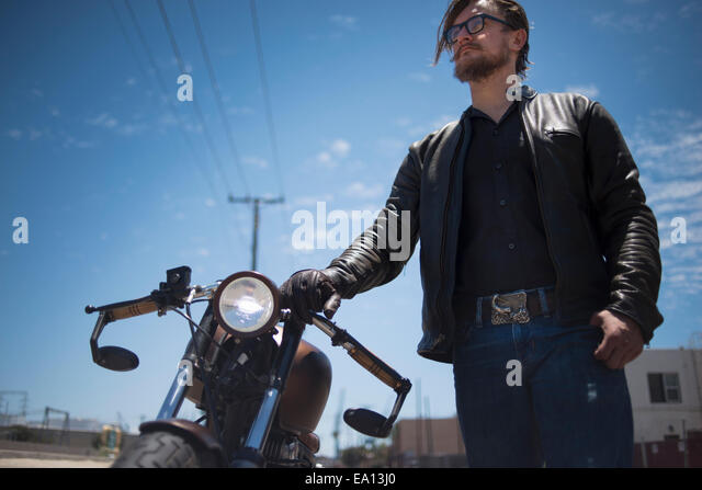 Low angled portrait of male hipster motorcyclist - Stock-Bilder