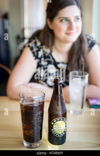 A glass and bottle of Boylan's Birch Beer, a soda manufactured by Boylan Bottling Company. - Stock Image