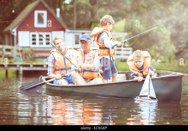 Brothers, father and grandfather fishing from canoe on lake - Stock Image