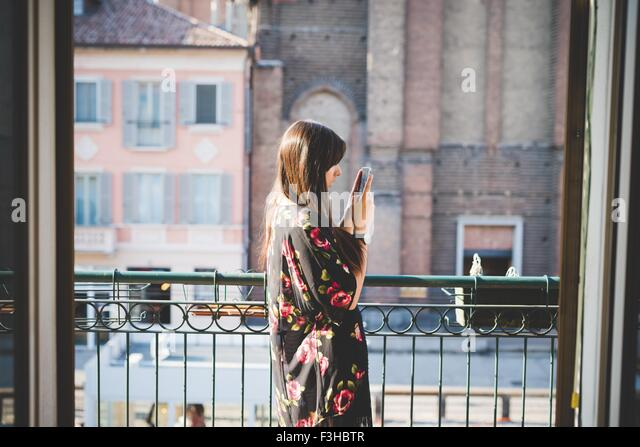 Young woman reading smartphone texts on city balcony - Stock Image
