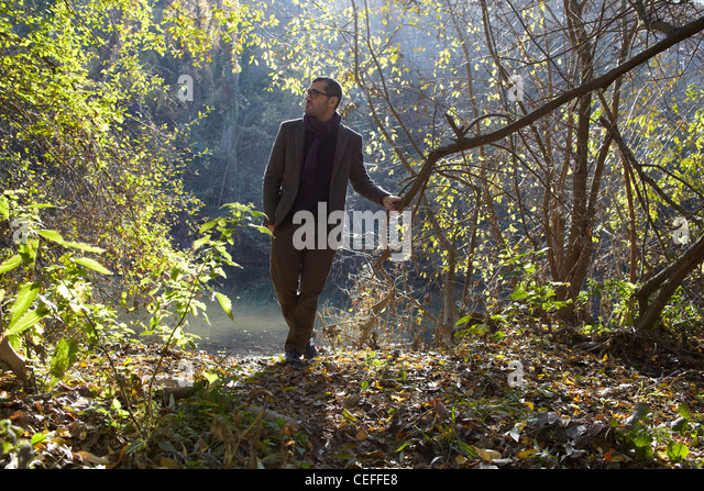 Man walking in forest - Stock Image