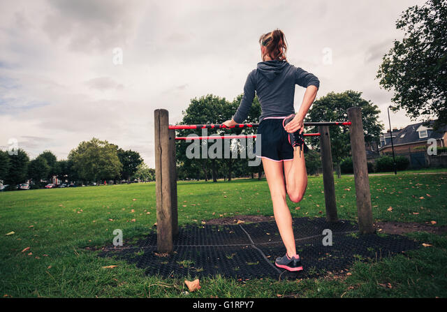 A young woman is stretching her legs on fitness equipment in the park - Stock Image