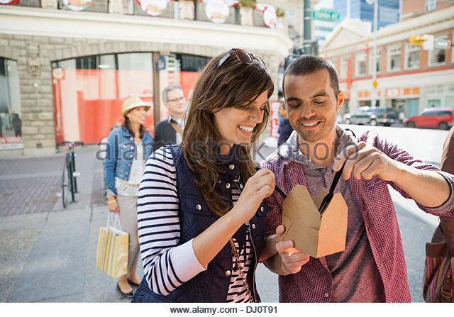 Couple sharing a meal from a food truck - Stock Image