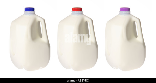 Three milk jugs with different color caps. - Stock Image