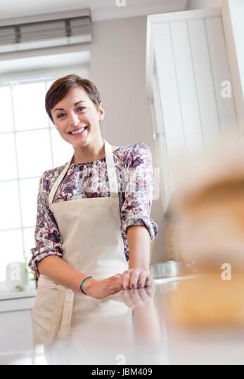 Portrait smiling brunette woman in apron in kitchen - Stock-Bilder