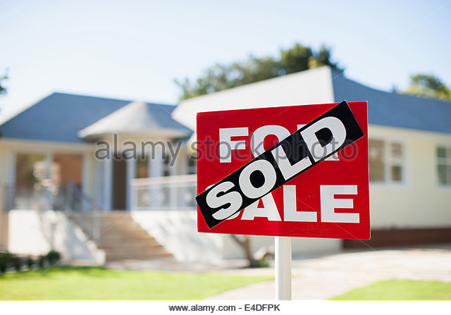 For sale sign in yard of house - Stock Image