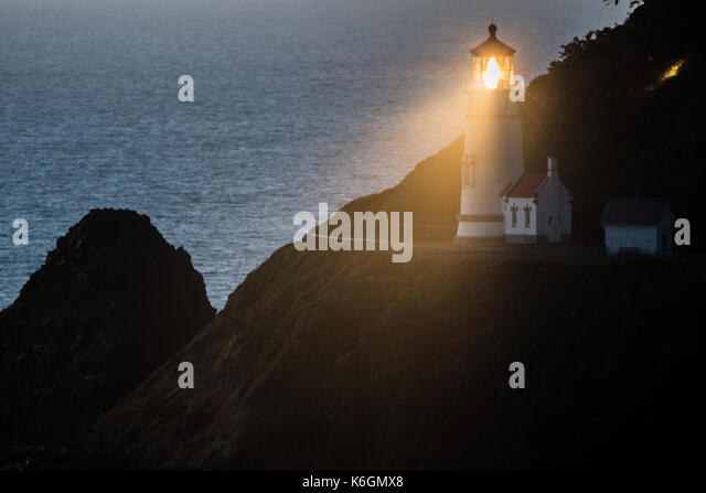 The Light of Heceta Head Lighthouse Shines at Dusk along the Oregon coast - Stock Image