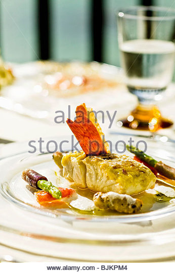 Red snapper with aioli, olive gnocchi and green asparagus - Stock Image