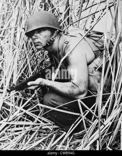 Soldier in grass, circa early 1940s. - Stock Image