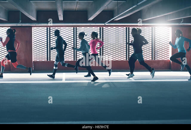 Group of diverse young people urban running in front of the brightly lit grids on the windows of an undercover parking - Stock Image