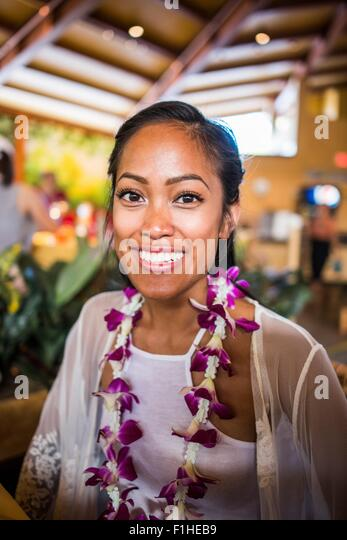 Portrait of young woman wearing flower lei in Polynesian Cultural Centre, Hawaii, USA - Stock Image