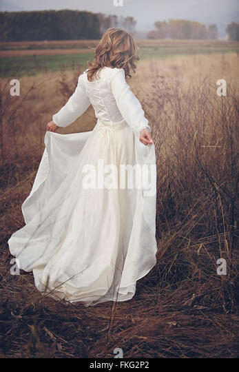 Woman with vintage dress in dry fields. Romance and purity - Stock Image