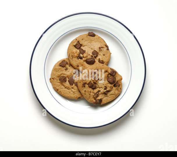 Three chocolate chip cookies on a round white dinner plate - Stock Image