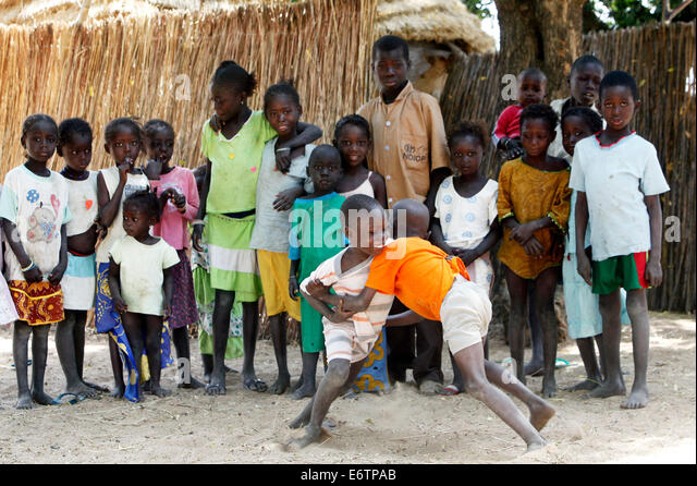 Children carry out a wrestling match. Wrestling is the senegalese national sport. Senegal, Africa - Stock Image