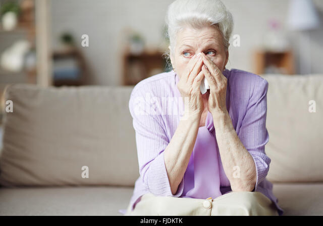 Sad senior woman sitting on sofa and crying - Stock Image