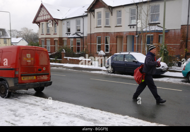 Postman delivering post in snow covered street in Bovey Tracey Devon england - Stock Image