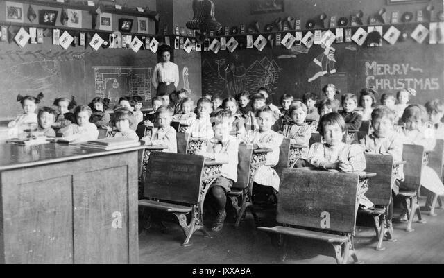 Full length landscape shot of schoolchildren sitting at desks, African American teacher in the back of the room, - Stock Image