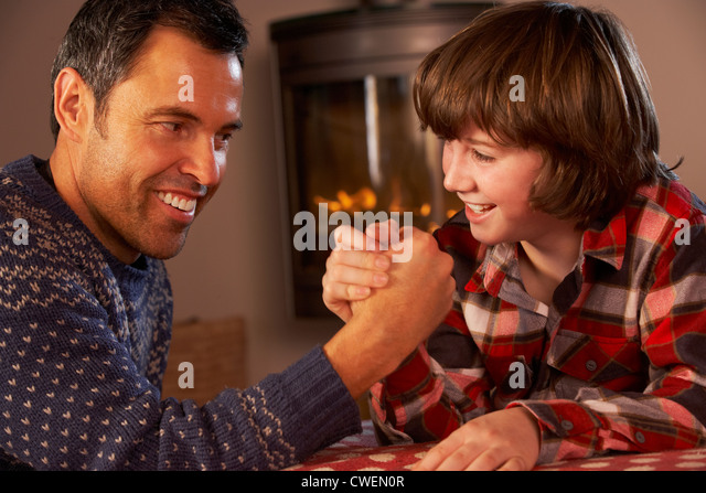 Father And Son Arm Wrestling By Cosy Log Fire - Stock Image