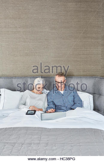Mature married couple using laptop together. - Stock Image