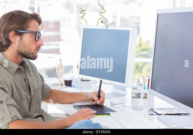 Graphic artist using graphics tablet - Stock Image
