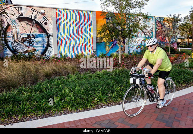 Gainesville Florida SW Depot Avenue wall mural art senior woman riding bicycle bike - Stock Image