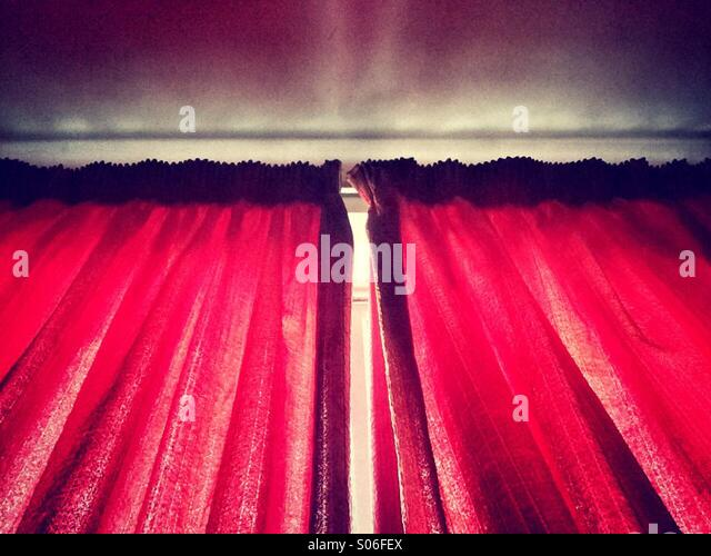 Sunlight streaming in though red curtains - Stock Image