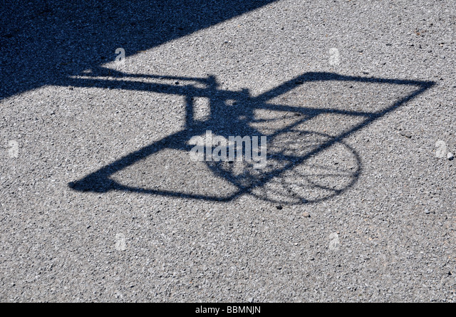Shadow of basket ball hoop on blacktop. - Stock Image