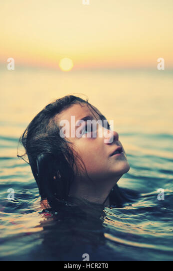 Young girl in red dress standing in sea at sunset - Stock Image