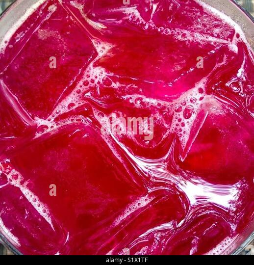 Close-up of red cranberry cocktail drink with ice cubes - Stock Image
