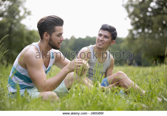 Two Male Friends Sitting In Summer Field Together - Stock-Bilder
