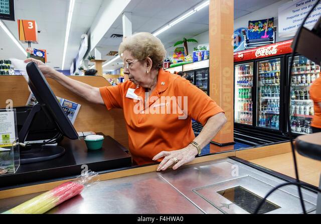 Miami Florida Navarro Discount Pharmacy drugstore inside shopping cashier checkout Hispanic senior woman employee - Stock Image