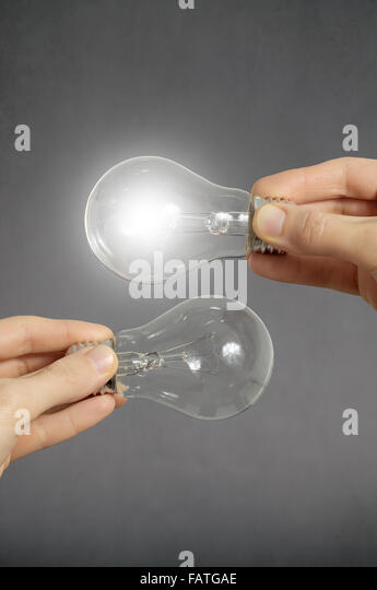 Decision making concept. Hands holding two light bulbs, one of them is glowing. - Stock Image