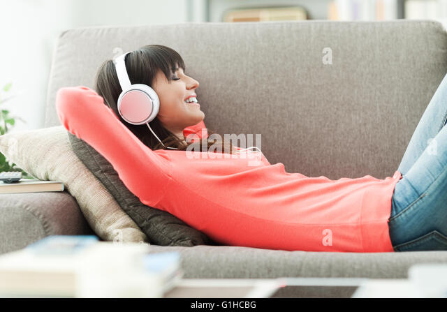 Young attractive woman relaxing on the couch at home, she is listening to music with headphones - Stock-Bilder
