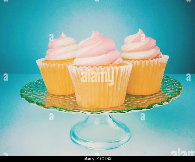 Vanilla strawberry buttercream frosted cupcakes on a glass serving platter. Space for copy. - Stock-Bilder